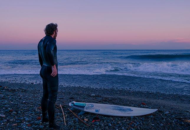 Surfer sulla spiaggia al crepuscolo